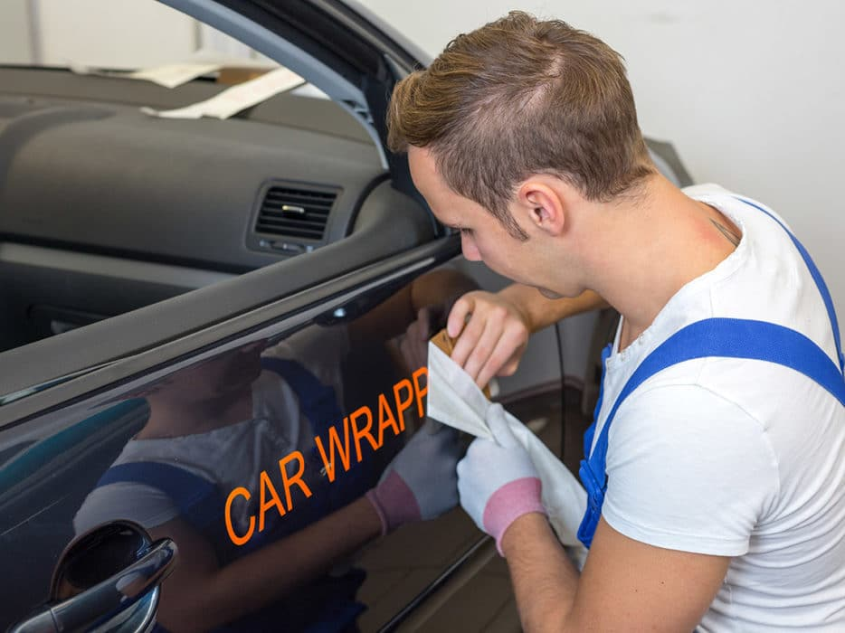 Car branding specialist puts logo with car wrapping vinyl on auto